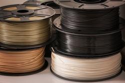 Many spools of 3D printer plastic filaments.
