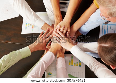 Many stacked hands from above as symbol for cooperation in the office