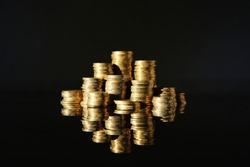 Many stacks of coins on mirror surface against black background