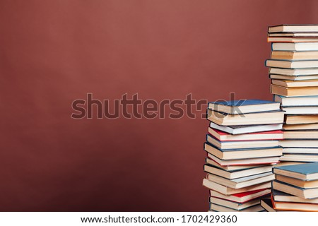 many stacks of educational books to study in the university library on a brown background