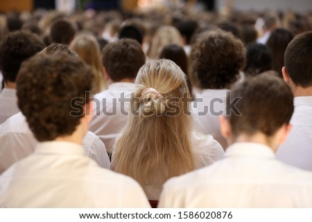 Many students sitting at a formal senior high school assembly presentation in the college hall. Female long blonde hair focus of image. Educational education theme