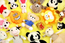 Many stuffed toys on yellow background, top view.
