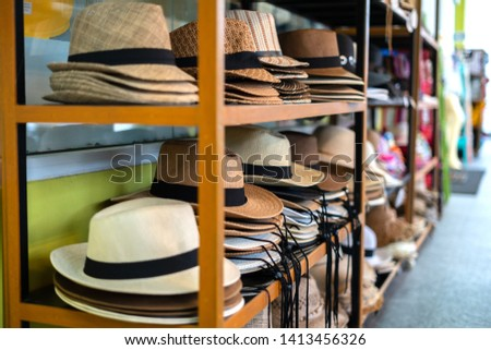 695ab389e58cfd many summer hats and Panama hats lie on the counter in the shop for tourists .