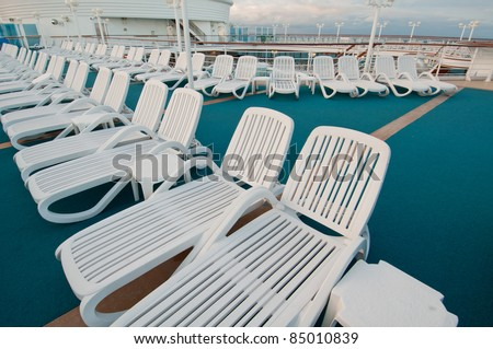 Many sun tanning beach chairs on top deck of cruise ship.