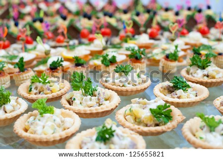 many tartlets with meat salad on buffet table