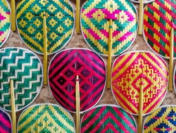 Many Thai style colorful wooden handmade fan arrange on the wall.