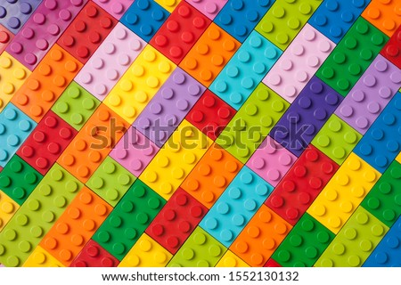 Photo of  Many toy blocks in different colors making up one large square shape in top view. Toys and games. Leisure and recreation.