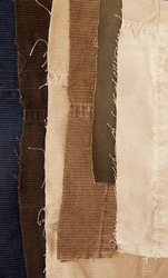 Many traditional corduroy and cotton retail as backdrop, with tattered around, against white background