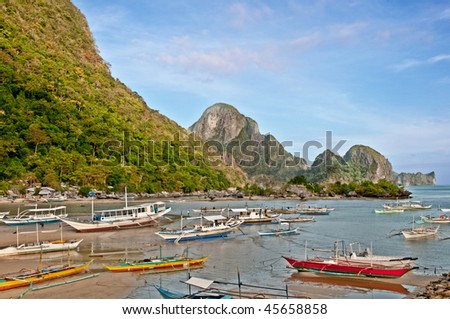 many traditional philippino boats in a bay