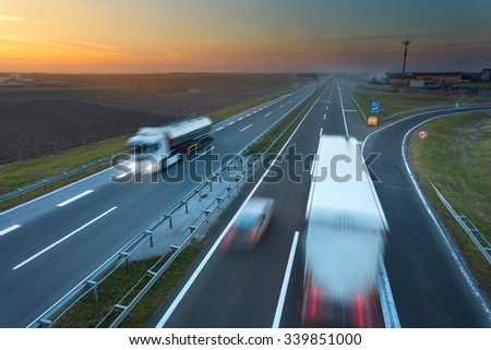 Many trucks driving in motion blur on the freeway at beautiful sunset. Rush hour on the highway near Belgrade - Serbia.