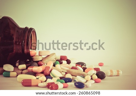Many type of medical drugs pills capsules and medicine poring from the bottle with  isolation background in vintage retro color. Used for manufacturing health industry concept.
