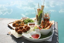 Many types of food styles, the cheese breads, Classic Thai Chicken Satay, chilli sauce in the glasses, Thai homemade fried spring rolls with shrimps and meatballs, noodles fried with chicken.