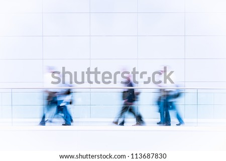 Many unrecognizable business people in a fair hall, intentional motion blur, blue tinted high resolution stock photo - stock photo