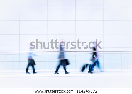 Many unrecognizable business people in front of modern architecture, intentional motion blur, blue tinted high resolution stock photo