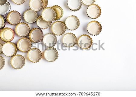 many upturned lids from beer scattered on a white background, space for text