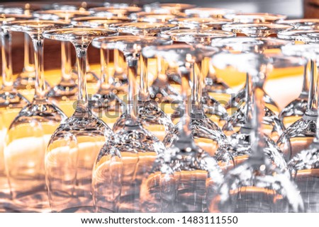 Many upturned wine glasses on table close up