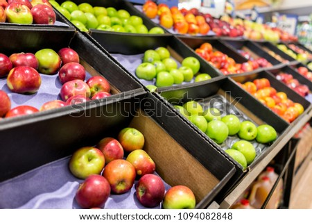 Many varieties assorted apples on display shelf in grocery store boxes in aisle, supermarket inside, nobody, including granny smith green and macintosh red fruit #1094082848