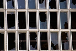 Many vertical window panes have been smashed and reveal a dark workshop with a few pieces of rusty iron. The pattern of the windows is broken by the smashed glass.