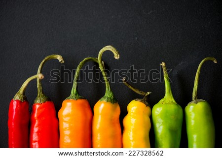 many vibrant colors on peppers on black slate background