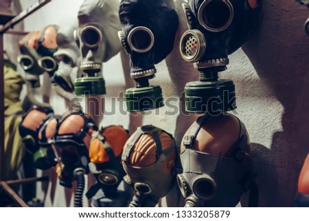 Many vintage old gas masks on wall in bomb shelter, close up