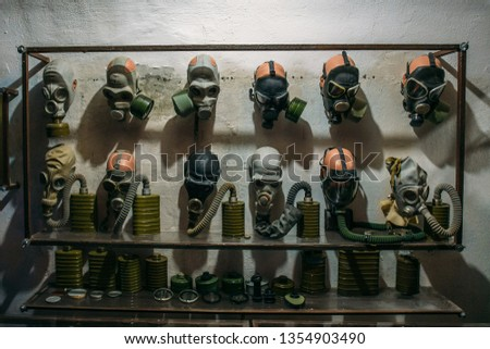 Many vintage old Soviet Gas Masks on wall in bomb shelter, close up