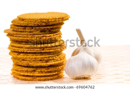 Many wafers and garlic lying on beige mat. Food snack prepared and ready to eat, standing on mat on table, zoom, horizontal orientation, objects in studio shot, front view.