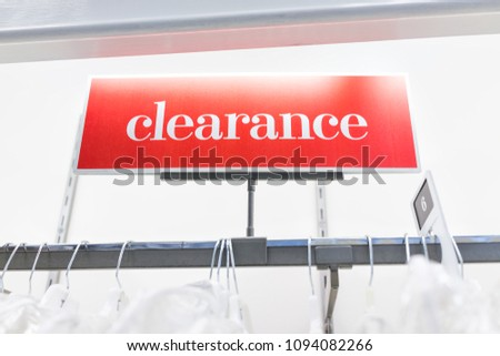 Many wedding dresses or clothes in boutique discount store, white garments hanging on rack hangers row closeup with large red clearance sign and size six, 6 #1094082266