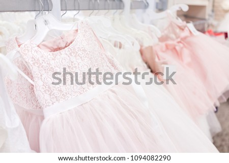 Many wedding flower girl party dresses in boutique discount store, pink garments hanging on rack hangers row closeup with white lace, tulle, design #1094082290