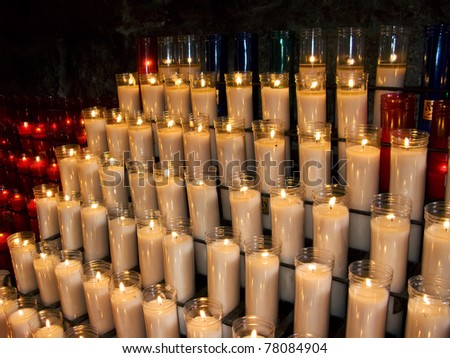 Many white and red church candles in a prayer