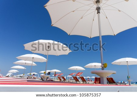 many white beach umbrellas and chairs on Rimini beach, Italy