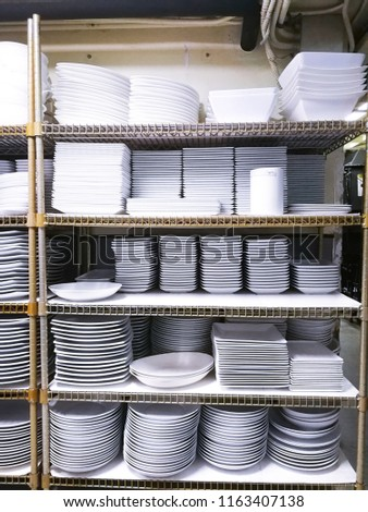 Many white ceramic plate on the shelves in store room