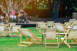 Many white deck chairs with tables for dinner in lawn is surrounded by shady green grass with blurred image of musical performance on stage in background.Comfortable on outdoor patio chairs in garden.