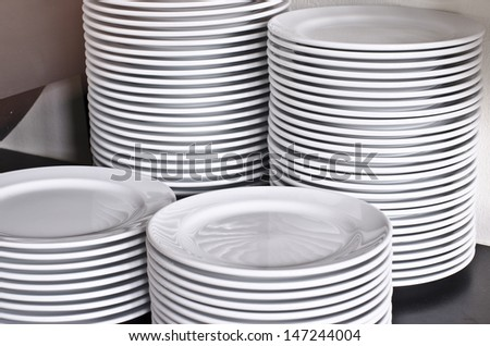 Many white different plates stacked together.