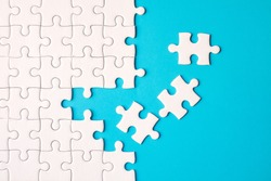 Many white jigsaw puzzle on blue background - idea solution concept.
