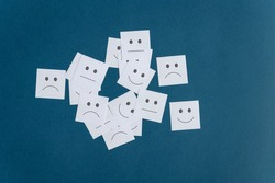 Many white post it papers with smiling sad and neutral faces on them. Over blue background.