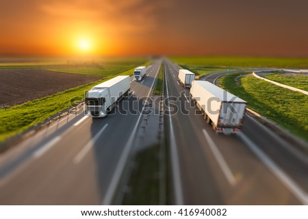 Many white trucks driving towards the sun. Fast blurred motion driving on the freeway in tilt shift technique. Freight scene on the motorway near Belgrade, Serbia. - stock photo