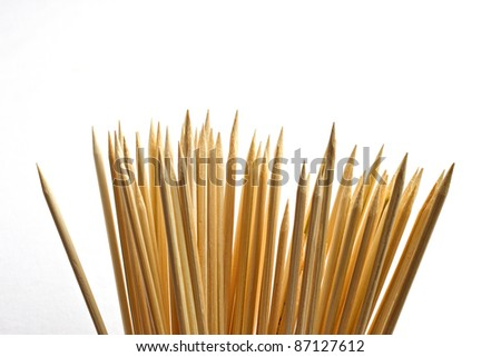 Many wooden bamboo skewers against solid white background - stock photo