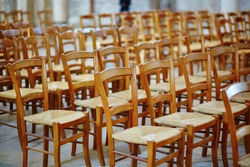 Many wooden chairs in a French church