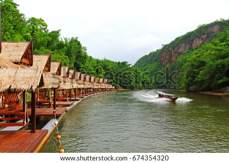 Many wooden house floating on the river with mountain and speed boat at Float house river kwai resort, Kanchanaburi, Thailand. Rest place, Landmark and Relaxing among beauty in nature concept Stok fotoğraf ©