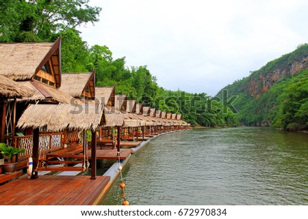 Many wooden house floating on the river with mountain at Float house river kwai resort, Kanchanaburi, Thailand