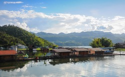 Many wooden houses float on the river by the Srinakarin Dam along with mountains in Kanchanaburi.