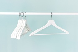 Many wooden white hangers on a rod, isolated on blue turquoise wall background. Store concept, sale, design, empty hanger. Place for your text