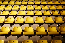 many yellow chairs with harsh light from side
