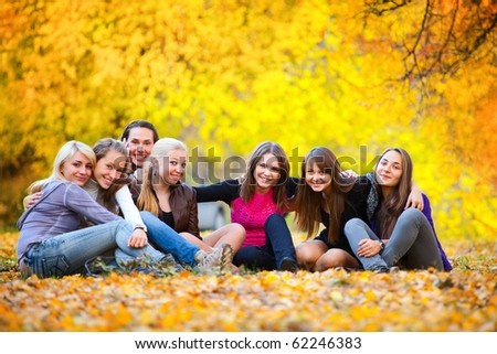 many young girls in the autumn park sitting on the grass