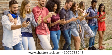 many young people using smart phones standing agaist a wall outside. concept of addiction to phone and gadgets wide header image