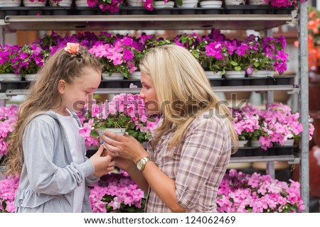 Maothe and daughter smelling plant in garden center