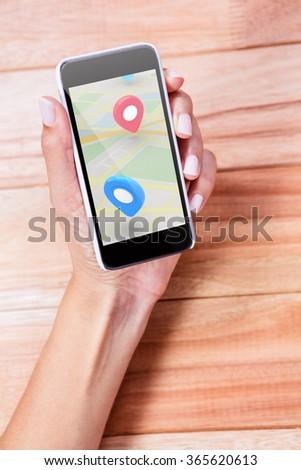 Map against feminine hand holding smartphone #365620613