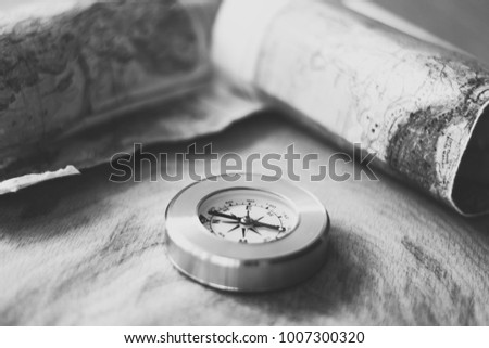 Map and compass lying on wooden background, black and white photo