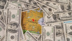 Map Canada covered in money, bank notes of one hundred dollars.