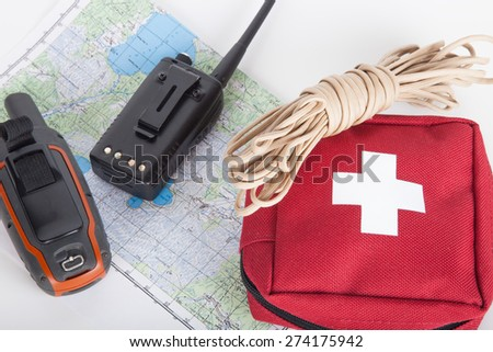 Map, gps navigator, portable radio, rope and first aid kit on a light background. Set lifeguard